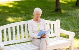Senior woman reading book at summer park. Old age, retirement and people concept - senior woman reading book sitting on bench at summer park Stock Images