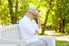 Thoughtful senior man sitting at summer park Royalty Free Stock Image