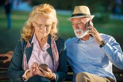 Old age, technology and people concept - happy senior couple with smartphones at summer park.  royalty free stock image