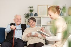 Old age tender couple laughing. Old age tender couple sitting together on a sofa and enjoying their time laughing while a healthcare personnel is reading to them royalty free stock images