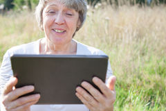 Old age woman using tablet device Stock Image