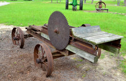 Old Aged Antique Mill Saw. Old rusty antique mill saw with old tractor and antique wheel sitting in the background in green grassy field Stock Image