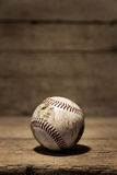 Old aged baseball in front of wooden background Stock Image