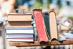 Old aged books at flea market. Vintage retro literature on wooden table outdoors. Street swap meet background.  royalty free stock image