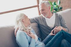 Old aged, caucasianleisure, happy senior couple enjoying time t. Ogether, looking to each other, laughing, sitting in living room on couch, woman`s legs lying on stock photos