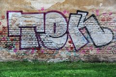 Old and aged color graffiti drawing on the wall. Stock Image