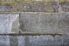 Old aged gray wall of large concrete blocks with small stones. rough surface texture. A old aged gray wall of large concrete blocks with small stones. rough royalty free stock image