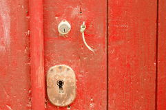 Old aged keyhole. Old red painted wood door metal keyhole with strap Royalty Free Stock Image