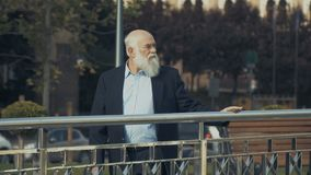Old-aged man walks near the railing. The camera moves from the right to the left. Old gray-haired man wearing suit is outdoors in the city. Intelligent elderly stock video footage