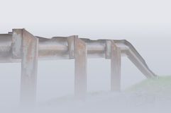 Old aged rusty grunge metallic bridge rail in mist Stock Images