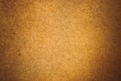 Old aged suede leather background. Coarse texture, gradient yellow brown beige, vivid colors. Stock Image
