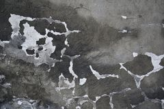 Old aged wall with crack. Ed and damaged plastering. Abstract dark surface with white bright holes. Deterioration of black and white material Royalty Free Stock Images