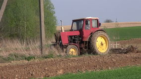 Old agriculture tractor cultivated field in spring stock video