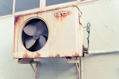 Old air compressor with rust. On the wall outdoor Stock Photography