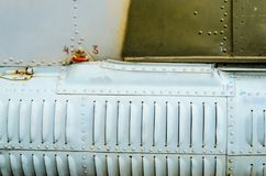 Old aircraft fuselage close up. Door handle and rivets Stock Image