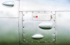 Old aircraft fuselage close up. Door handle and rivets Stock Photography