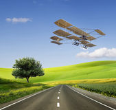 Old aircraft on the green field and road Royalty Free Stock Photo