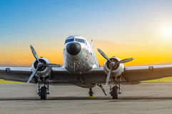 Old aircraft at sunset at the airport parking.  Royalty Free Stock Images