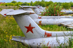 Old aircrafts in elderberry bush, Aero L-29 Delfin Maya czechoslovakian military jet trainer. On an abandoned airfield in Ukraine royalty free stock photos