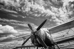Old airplane on field in black and white. Beautifull sky Royalty Free Stock Images