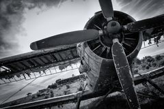 Old airplane on field in black and white. Cloudy sky Stock Image