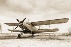 Old airplane. On field in sepia tone Royalty Free Stock Photography