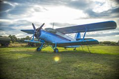 Old airplane. On green grass and sunset background Stock Photo