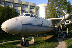 Old airplane near building. Old airplane or aircraft with propellers on grass outside modern urban building Stock Images