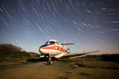 Old airplane at night with star trails Royalty Free Stock Photos