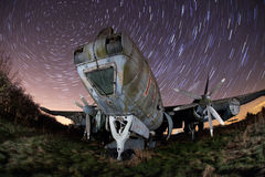 Old airplane at night with star trails. Old plane disused in an old airfield at night with star trails Royalty Free Stock Photos