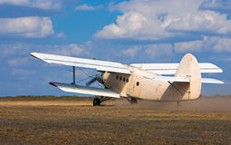 Old airplane takes off on the field Royalty Free Stock Photography