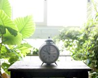 Old alarm bell clock at the window backlit Royalty Free Stock Image