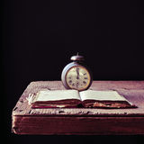 Old alarm clock and book on a rustic wooden table Royalty Free Stock Images