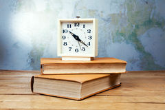 Old alarm clock with books Stock Photo