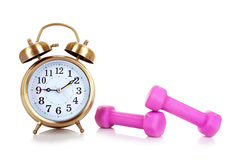 Old alarm-clock and dumbbells isolated Royalty Free Stock Images