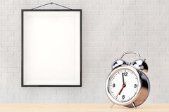 Old Alarm Clock in front of Brick Wall with Blank Frame Royalty Free Stock Photography