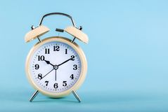 Old alarm clock isolated on a blue background with space for text Stock Image