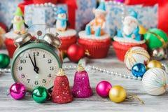 Old alarm clock near Christmas colored decorations Stock Photos