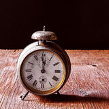 Old alarm clock on a rustic wooden table Royalty Free Stock Image