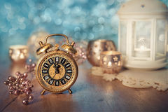 Old alarm clock set to five to midnight. Happy New Year!. Old alarm clock set to five to midnight on decorated table with candles. Happy New Year Royalty Free Stock Images