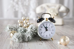 Old alarm clock showing five to midnight and white vintage phone Royalty Free Stock Photos
