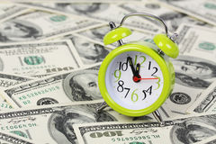 Old alarm clock standing on background of money Stock Photography