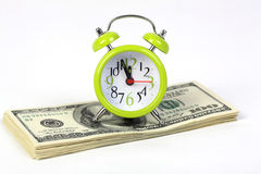 Old alarm clock standing on stack of money Royalty Free Stock Photos