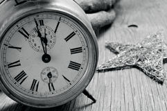 Old alarm clock and star on a rustic wooden surface, in black an. And old alarm clock and a star on a rustic wooden surface, in black and white Stock Images