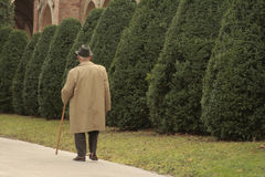 Old and alone. Old man in city walking in the city garden Stock Image