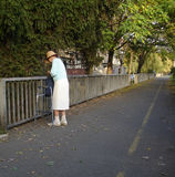 Old and alone lady. Old and handicapped lady walking slowly on the sunny autumn day Royalty Free Stock Photos