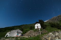 Old alpine rural settlement with startrail Stock Photo