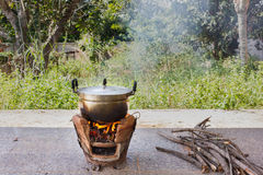 Old aluminium pot on stove with fire and smoke, folk cooking way Stock Photos