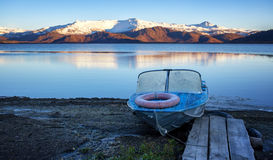 Old aluminum boat on lake shore Royalty Free Stock Images