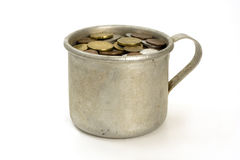 Old aluminum mug and coins. Royalty Free Stock Image